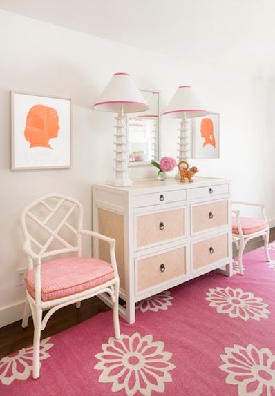 Orange and pink girl's bedroom features a dresser fitted with linen covered drawers topped with White Pagoda Lamps flanked by orange silhouette prints over white bamboo chairs lined with pink cushions atop a pink floral rug.
