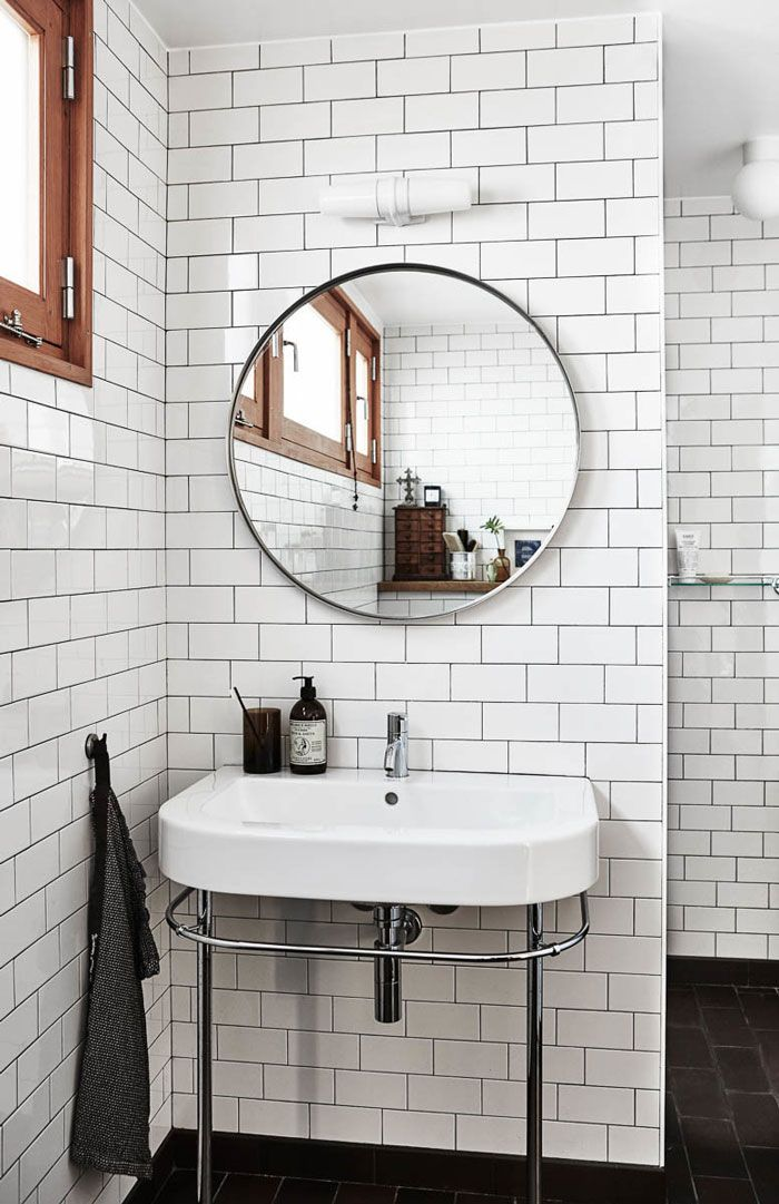white subway tile with black grout round mirror and black floor tiles for the perfect balance of simplicity in the bathroom - Mirror Tile Bathroom Decor