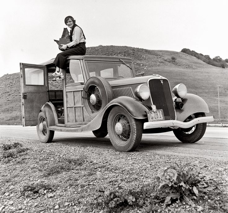 Dorothea Lange, Resettlement Administration photographer, in California atop car with her giant camera. February 1936