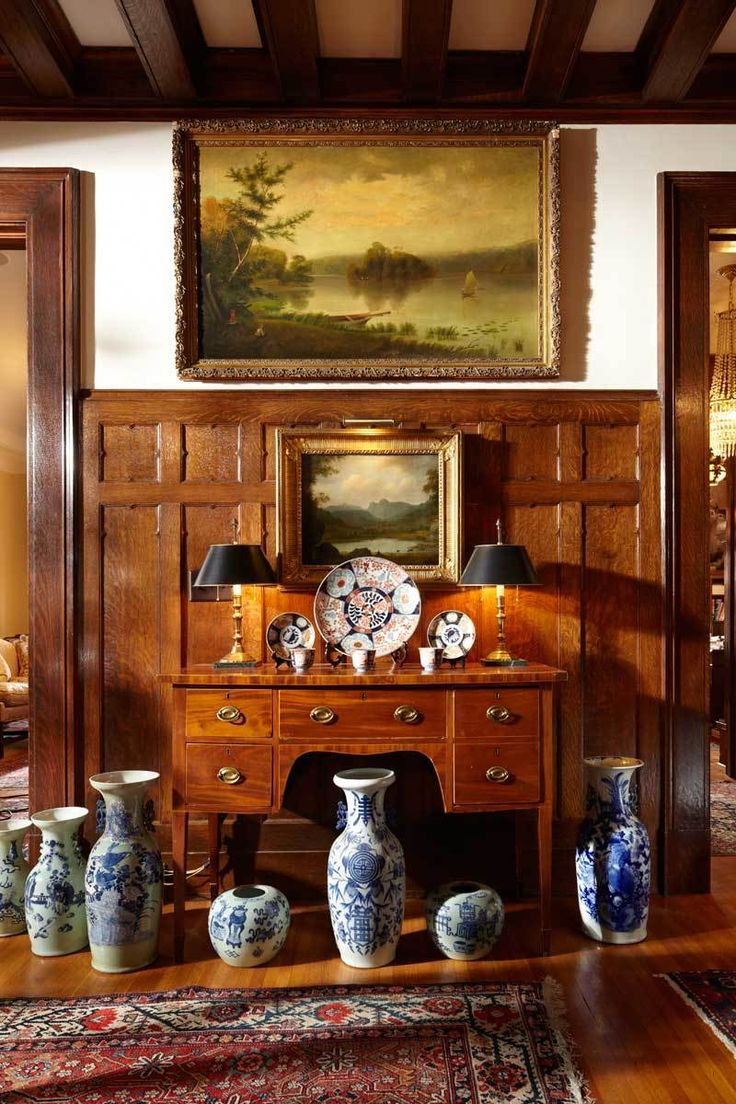A Hudson River School painting hangs in the foyer, over a collection of Imari porcelain and Chinese vases that stands out against the oak wainscot.