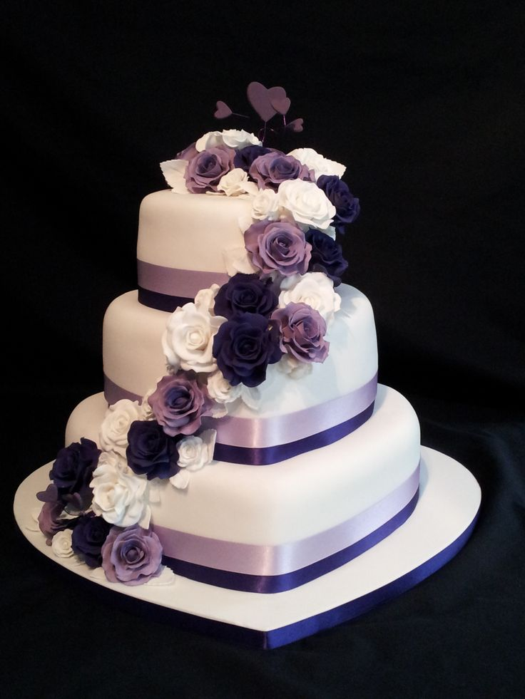3 tier heart shaped wedding cake. roses cascading down with a purple theme.                                                                                                                                                      More