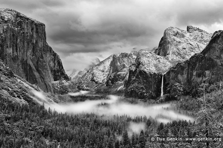 Yosemite Valley and Bridalveil Falls from Tunnel View, Yosemite National Park, California, USA. Black and white photo of the Yosemite Valley and Bridalveil Falls from Tunnel View early in the morning. Snow covered peaks, mountains and trees and morning fog is laying in the valley. Tunnel View, within Yosemite National Park, is a viewpoint on State Route 41 located directly east of the Wawona Tunnel as one enters Yosemite Valley from the South. The view looks east into Yosemite Valley…