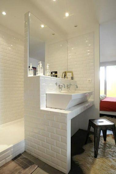 On n'y pense pas forcément et pourtant les parois de douche peuvent être nos meilleures alliées quand il s'agit de rangement dans une petite salle de bain ! Ici, juste devant le miroir, la cloison en carrelage métro blanc au dessus du lavabo offre un petit espace idéal et semble fait sur mesure pour accueillir les produits de beauté de Madame. Une salle de bain pleine de charme où tout l'espace est optimisé.