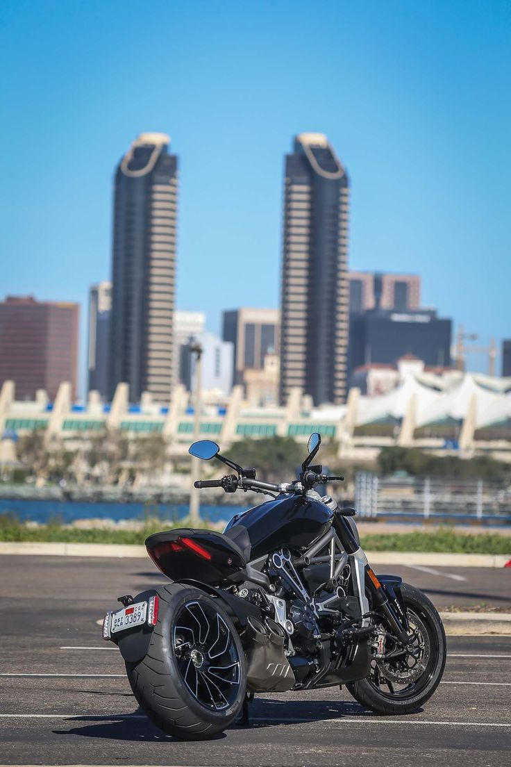 """The Ducati XDiavel is the latest push by the Italian manufacturer into a market dominated by American brands. The XDiavel evolves the Diavel aesthetic, with its longer and lower power cruiser lines, and the controversial addition of forward-controls and a belt final-drive. The XDiavel model is designed to evangelize non-Ducati riders into the Italian company, and as such the XDiavel sits somewhere between the Ducati Scrambler and other more """"traditional"""" Ducati models, in terms of its…"""