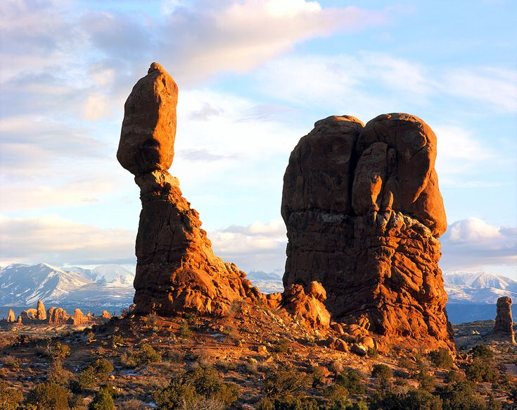 These balancing rocks in Utah's Moab Desert formed because wind eroded the lower-down rock layers faster than it eroded the thicker caprock. Because earthquakes can topple these balancing rocks, their presence indicates that an area exhibits tectonic stability.