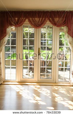 View From A Empty Room Showing Curtains And French UPVC Patio Doors With  Sun Shining Through