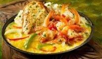 SIZZLING CHICKEN & SHRIMP Kurz gebratene, mit Knoblauch gewürzte Hühnerbrust und herrliche Shrimps in pikanter tomaten-Basilikum Salsa mit Zwiebel, Paprikaschoten und Cheddar Käse-Kartoffel-Püree, serviert auf einer heißen Platte mit geschmolzenem Colby- und Jack Käse.
