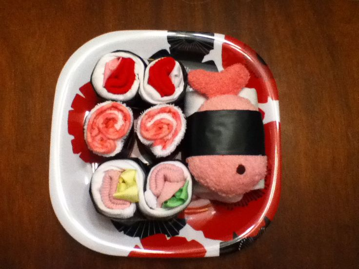 Sushi baby shower gift using towels, bows, toys and black plastic