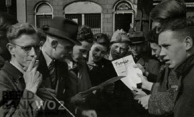 Publiek leest de krant 'Trouw' op bevrijdingsdag. 'bevrijdingsdag 's morgens +/- 8 uur bij de courant, De Trouw, gegeven bij mevr. Leny van Beek, v.d. Speld. Op de foto zijn no.2. dhr. de Raad. no.3. dhr. Wim Dijkstra. no.4. Toen Leny v.d. Speld, nu wonend in Amerika.'