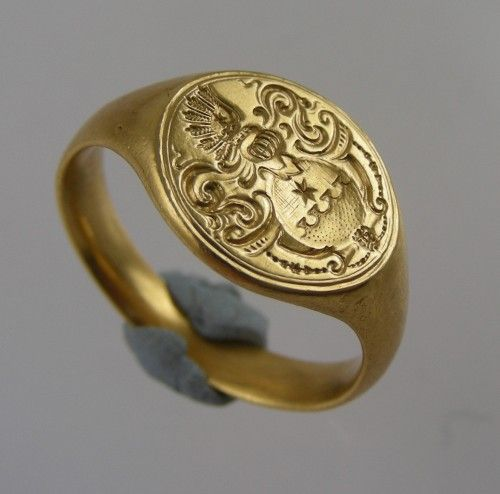 Seventeenth century gold armorial ring. Probably German ca. 1660. The bezel is seal engraved with a round shield,