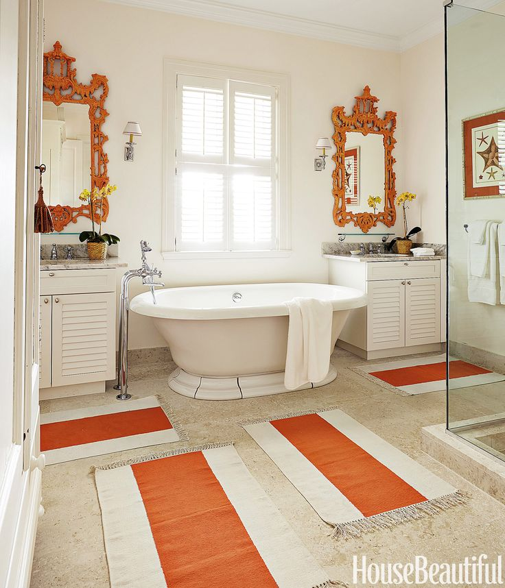 """Pagoda mirrors and Serena & Lily dhurries give """"a little jolt"""" to the master bath in a Bahamas house designed by Amanda Lindroth. Kohler tub with Waterworks fittings   - HouseBeautiful.com"""
