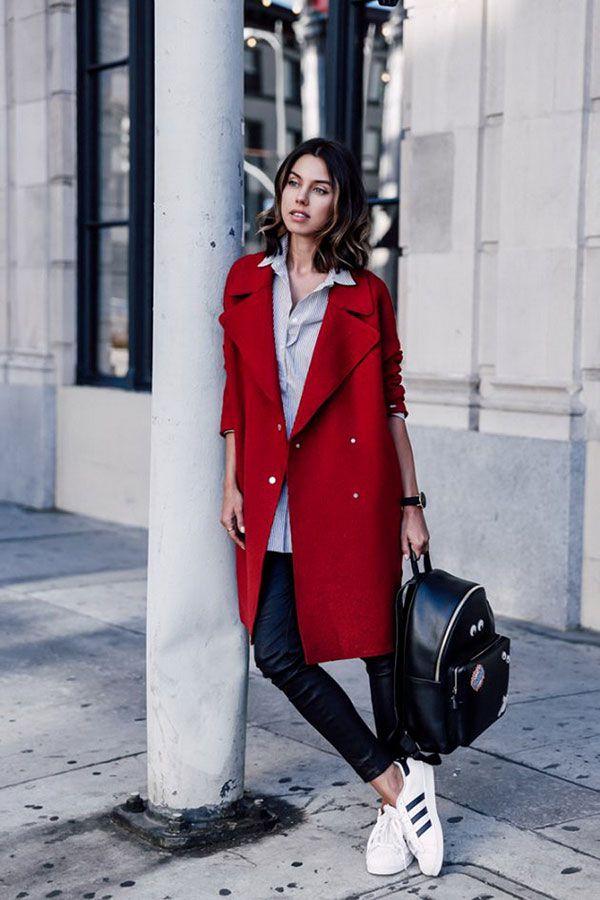 Annabelle Fleur usa calça de couro, camisa, overcoat vermelho, tênis branco e mochila de couro.