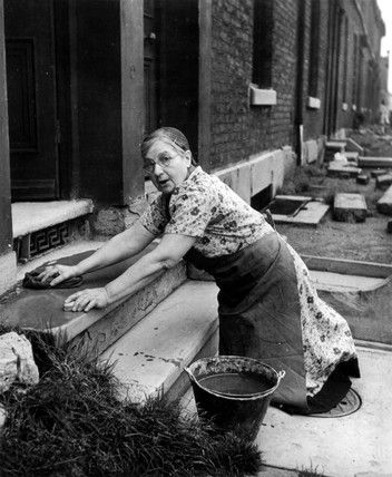 A woman in Dublin Ireland tenements giving the front doorstep of her house a good scrub