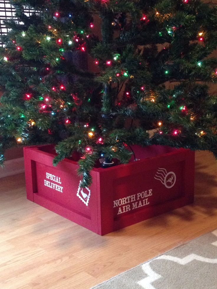 "Pic only. My husband and I built a Christmas tree stand ""crate"" to use instead of a tree skirt/dog hair magnet. There's still enough clearance for our tree to rotate in the rotating tree stand. It measures 20""x20""x10""h. Spray painted with Valspar Brilliant Red FLAT from Lowes. I cut vinyl with my Cricut and used them as stencils and filled them in with white craft paint. Christmas tree stand crate North Pole Air Mail"