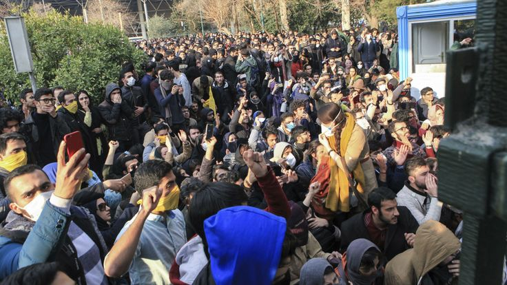 FILE - In this Saturday, Dec. 30, 2017 file photo taken by an individual not employed by the Associated Press and obtained by the AP outside Iran, university students attend a protest inside Tehran University while anti-riot Iranian police prevent them to join other protestors, in Tehran, Iran. As protests over Iran's faltering economy rapidly spread across the country, a channel on a mobile messaging app run by an exiled journalist helped fan the passions of some of those who took to the…
