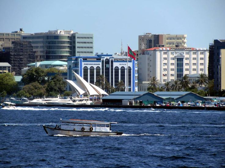 The national flag of the Maldives flies above Republic Square in the center of Male. The large white awnings shelter the Presidential Jetty.