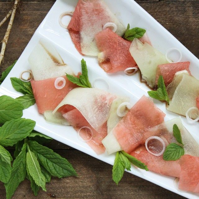 Thin slices of melon with spring onions and balsamic vinegarhellip