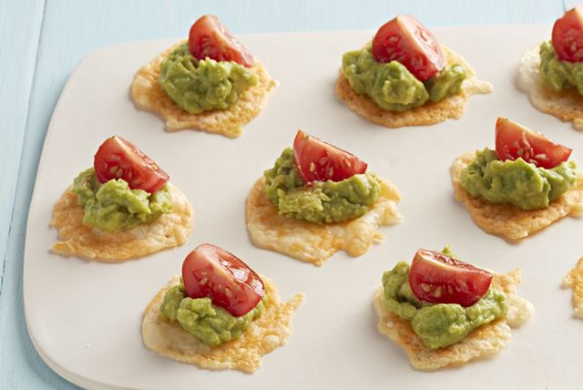 Homemade cheese crisps are a breeze to make—and they taste fantastic topped with creamy guacamole and fresh cherry tomatoes.