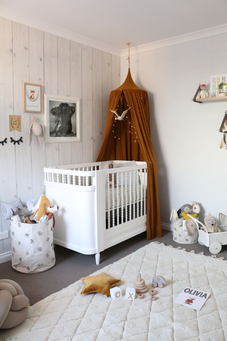 Gender neutral nursery room. Gold mustard canopy with wood look wall paper…