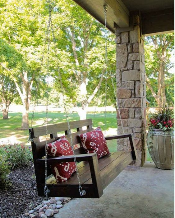 Деревянная лавочка-качеля на крыльце дома, создаст интересную атмосферу легкости и непринужденности.