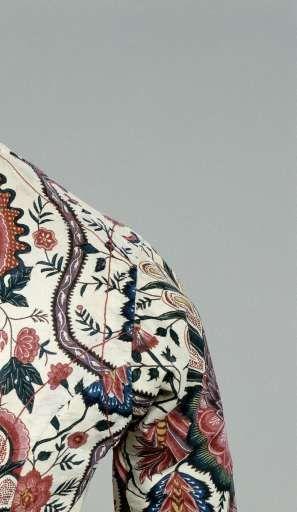 Jak van sits, dat op een crèmekleurig fond grote bloemen en ruitpatronen toont, met als hoofdkleuren paars, roze, blauw en blauwgroen. Afwerking met roze-wit langettenband., anoniem, 1810 - 1820 - Rijksmuseum