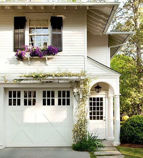 White Clapboard Siding   Arched Doorway   Carriage Garage Door   Pergola Over Garage   Black Shutters   Window Box