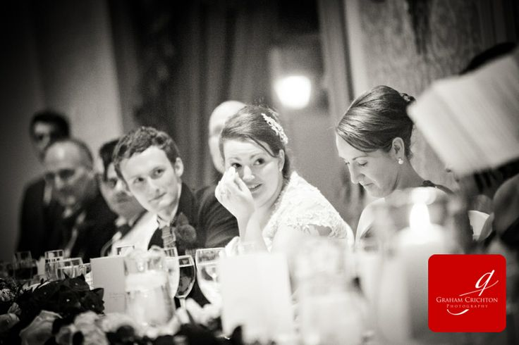 Bride wiping a tear from her eye during the wedding speeches www.grahamcrichton.com