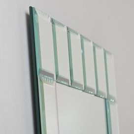"""Frameless mirror with a handmade beveled block edge.   Product: MirrorConstruction Material: Mirrored glass and metalColor: SilverFeatures: Hanging hardware includedDimensions: 31.5"""" H x 23.6"""" W x 0.5"""" D"""