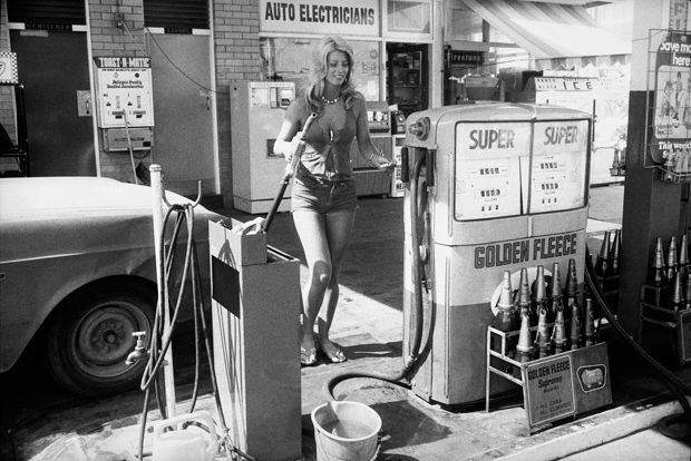 Female petrol pump assistant in Australia, photographed by Rennie Ellis, 1975