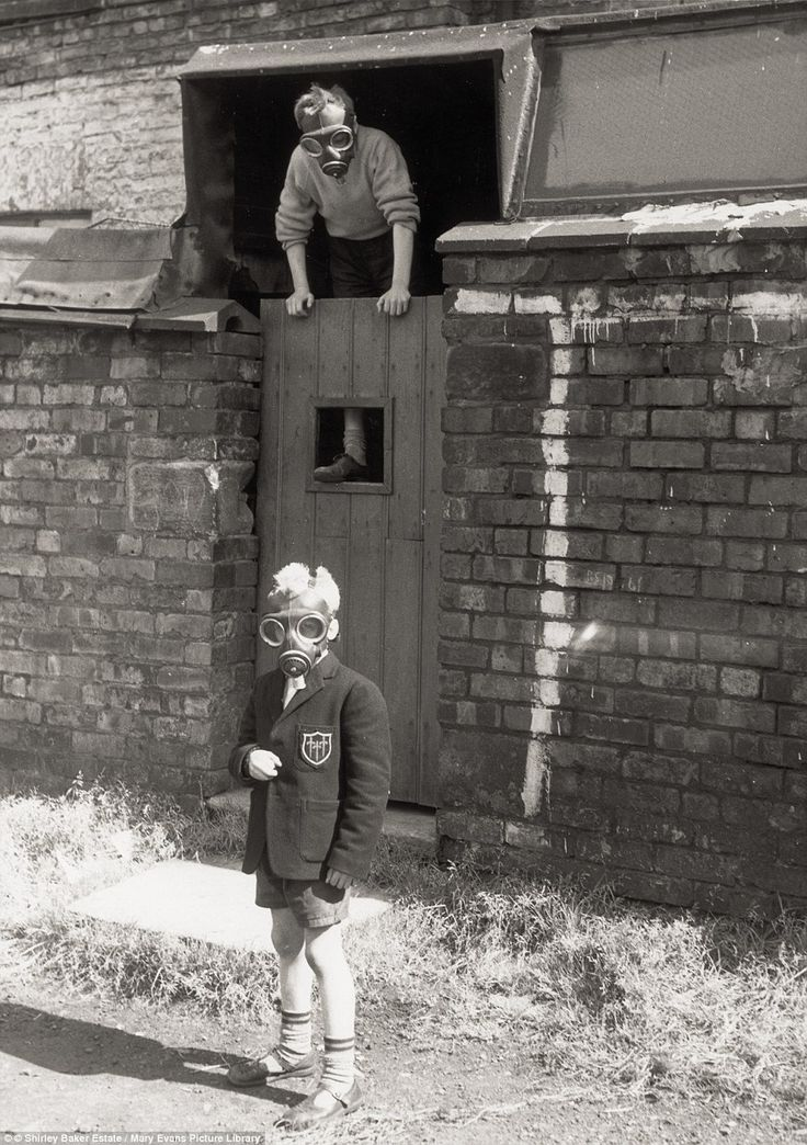 These two children are playing with a pair of Second World War surplus gas masks while one is still in his school blazer