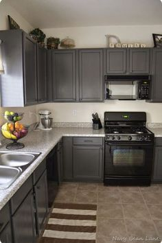 how to decorate a kitchen with black appliances and dark gray painted cabinets