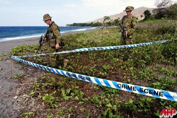 """LIQUICA, EAST TIMOR, 19-OCT-1999: Australian soldiers walk around a newly discovered mass grave on the beach at Liquica, 50km west of Dili October 19 1999. Authorities will attempt to exhume at least 20 bodies which have been located in three grave sites in and around the town of Liquica. [Photo by Rob Elliott, AFP]"""
