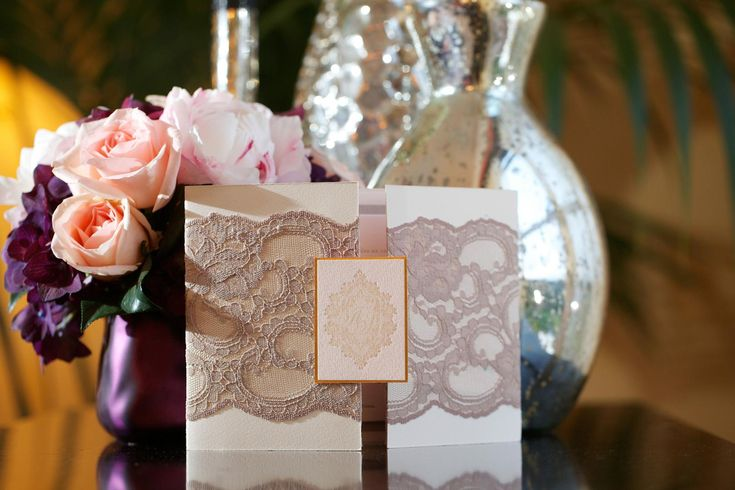 Elegant wedding invitations were embellished with champagne-hued lace and featured the couple's custom wedding monogram. #weddinginvitation #weddingstationery Photography: Bob & Dawn Davis Photography. Read More: http://www.insideweddings.com/weddings/ashley-hebert-and-jp-rosenbaum/438/