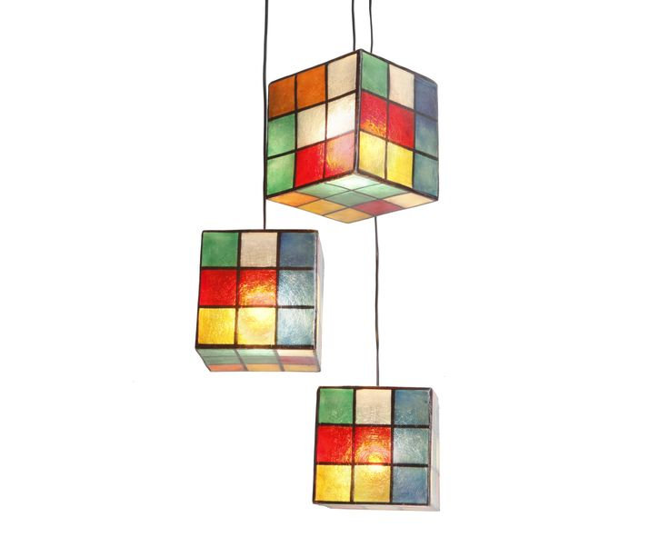 Lighting fixture in the shape of a cube, made out of fiberglass. It can be hung from the ceiling as the central lighting fixture of any space, or be put on any surface (table, shelf, floor) as a lamp standing on it own. Available in two colors: Color Rubik's and B&W Rubik's.  They come complete with an E14 bulb holder and you can use as much wattage as you need.Fiberglass can take as much wattage as you need.We use only 25W bulbs in our photos, so that their colors can be clearly…