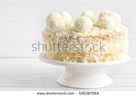 Coconut cake with coconut balls on top, white background.