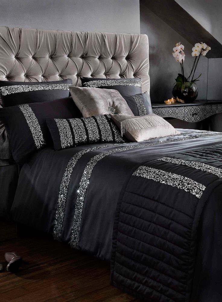 This sophisticated black satin effect bed linen from Kylie features silver…