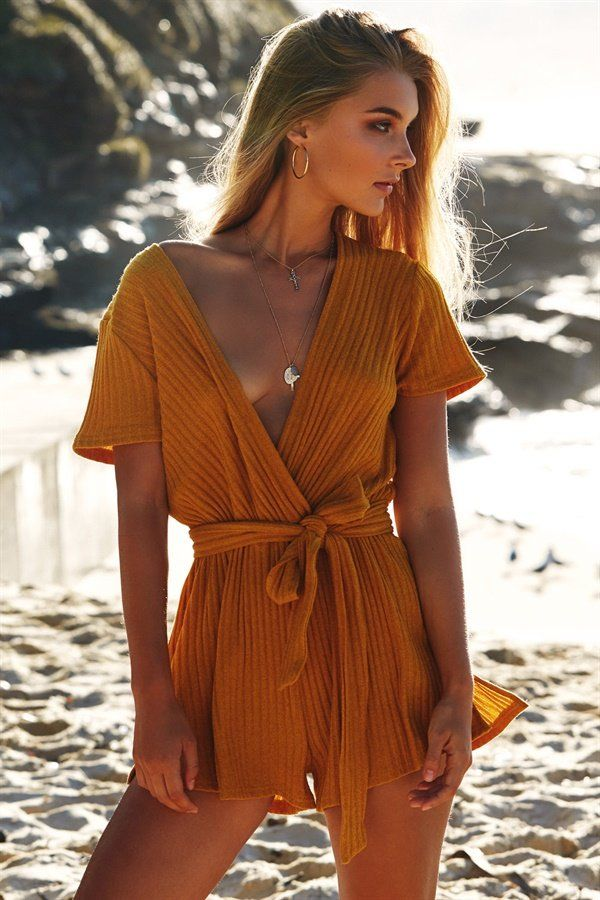 Stand out in the bold Knox Mustard Playsuit, made from a ribbed fabric in a mustard hue. It features a plunging V neckline, short sleeves, an elasticated waistband, twin splits in shorts and a matching waist tie. Complete the look with a fine gold necklace and boots! By Sabo Skirt.