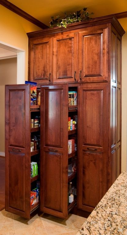 This cherry finished pull-out pantry looks like a very convenient way to stock groceries. This floor-to-ceiling pantry is divided into two tiers. On the lower tier are the pull-outs, while the shorter upper tier has cabinets for additional storage.