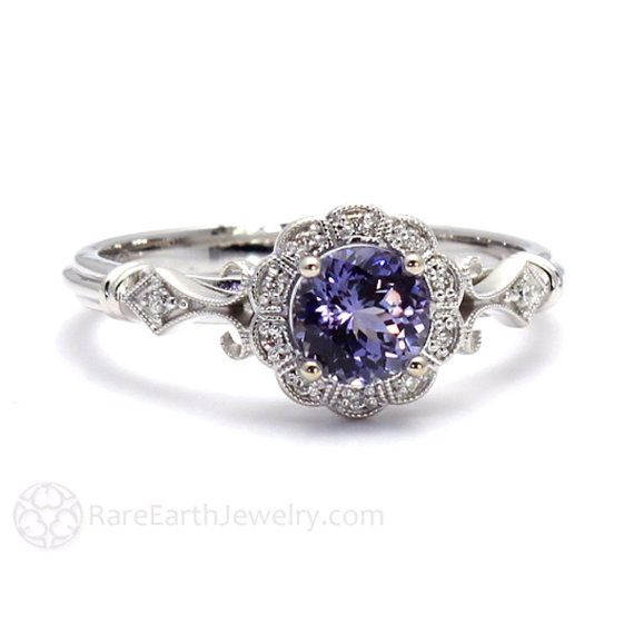 A uniquely lovely Purple Sapphire vintage inspired ring with a beautiful Art Deco design with milgrain detailing. At the center is a 1.05ct natural Purple Sapphire and there are .10ct of conflict free diamonds in the halo and accenting the shank. This ring is available in 14K or 18K White, Yellow or Rose Gold. Gorgeous!  A strong and durable gemstone, Sapphire is a perfect choice for everyday wear.  Official Website: www.RareEarthJewelry.com  ****SCHEDULE**** This ring is made to order and…
