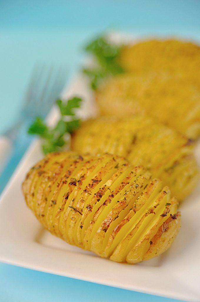 Bereiden: Schil de aardappelen, spoel ze af en leg ze in een houten lepel. Maak met een scherp mes inkepingen in de aardappel, ongeveer 3-6 mm van elkaar af, maar snij de aardappelen niet helemaal door. De lepel zal dit ook verhinderen. Leg de aardappelen met de ingesneden kant naar boven in een licht beboterde braadslede.