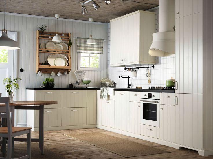 Luonnonvalkoinen country-tyylinen keittiö, jossa mustat työtasot sekä luonnonvalkoinen uuni ja liesituuletin.
