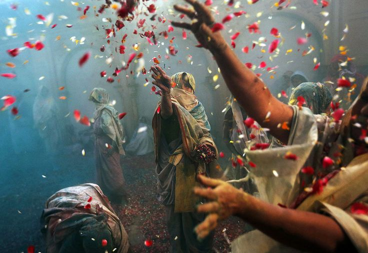 Vrindavan, India — Indian Hindu widows throw flowers as part of Holi celebrations organized by the NGO Sulabh at the Meera Sahbhagini Ashram. The widows, many of whom at times have lived in the streets of the temple town, celebrated the festival for the first time at the century-old ashram.  by Kevin Frayer (Associated Press)