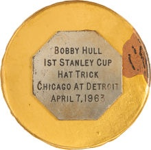 1963 Bobby Hull Game Used Puck from First Stanley Cup Playoffs Hat Trick, with plaque describing the accomplishment.