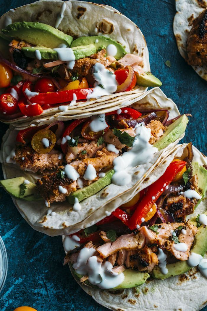 Blackened salmon fajitas filled with peppers, onions, avocado, and a cilantro lime sauce.
