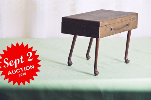 A special box with an interior freshly lined with textured wallpaper, and elevated on four animated mahogany legs.