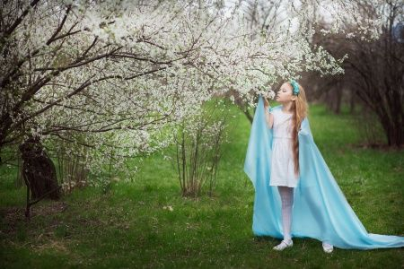 Девочка нюхает цветущее дерево