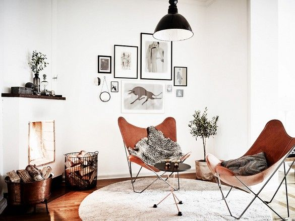 Brown leather butterfly chairs in front of a fireplace