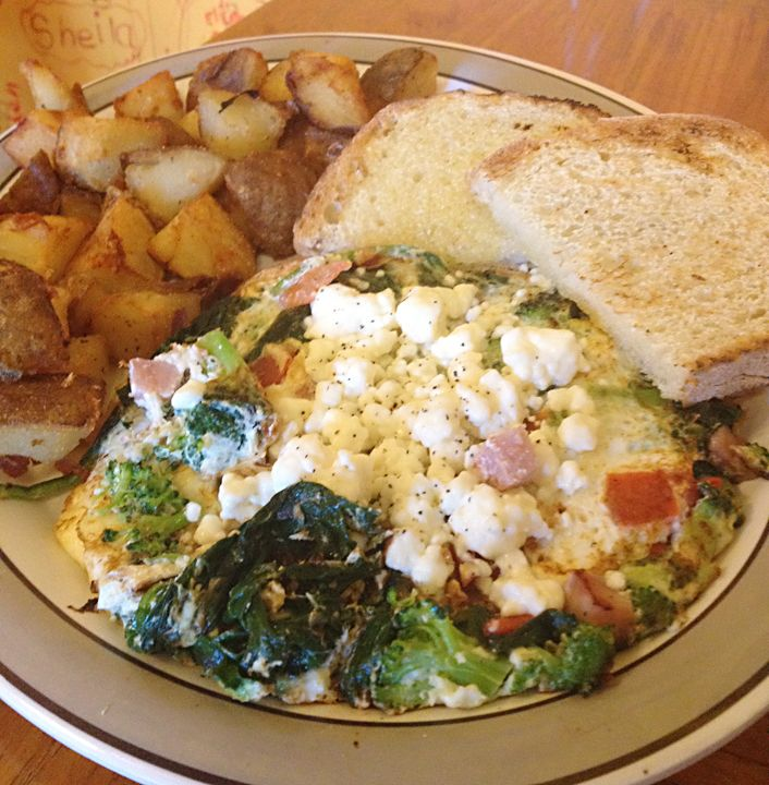 and ham topped with feta cheese spinach broccoli and tomatoes served ...