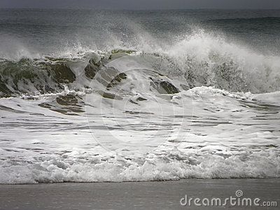 A view of rolling storm waves on the beach.
