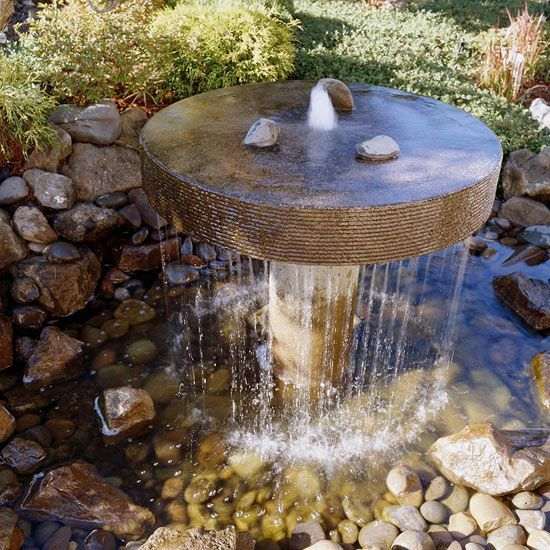 Fountains come in many different shapes and designs. This Japanese-influenced concrete fountain blends in beautifully with the stone-lined pond. The sheet of water that spills over the edge catches the sunlight while adding the soothing sound of running water. Supported by a central pedestal, water erupts from the center of the stone and then spills into the shallow pond below.